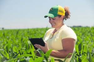 Girl in John Deere cap in field